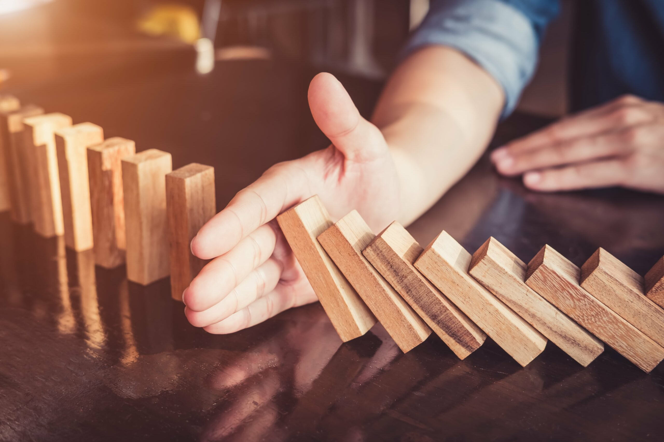 hand stopping dominos from falling to indicate the power of someone stopping the I'm not good at anything belief system